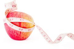 Big ripe red apple with measure tape. Big ripe red apple with white measure tape around it metaphore of healthy eating and diet Stock Images