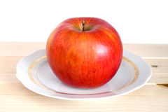 Big ripe red apple on white plate with gold trim in wooden shelf Stock Photos
