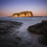 Big rock in the middle of the sea of Lombok with sunrise moment Stock Photo