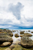 Big rock with ocean view and dark clouds Stock Image