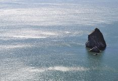 Big Rock in Shimmering Blue Water Stock Photos