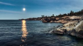 Big rock at sunset blue sea and moonlight in the distance stock photography