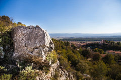Big rock with a view in southern France. A big rock in foreground with vineyards and mountain Sainte Baume in background. Puyloubier, Provence, Southern France royalty free stock photography