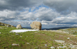 Big rocks on green mountain hill woth dark clouds on sky. Magnificent beautiful dramatic view Royalty Free Stock Photo