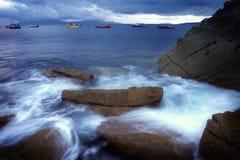 Big rocks at ocean shore. Idyllic bay with big rocks and anchoring boats during sun set on Isle of Skye, Scotland Royalty Free Stock Image