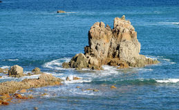 Big rocks in the sea surrounded by waves Stock Image