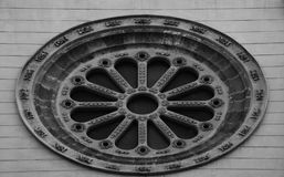 The big rosette is so beautiful. Shot in black and white, detail on the sculpture on the facade of this historic building representing some characters / animals Royalty Free Stock Images