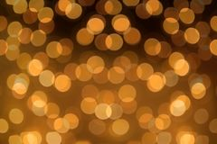 Big round Bokeh in golden yellow on dark brown background. Abstract Blurred circles. Background photo stock photography