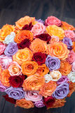 Big round bouquet of colorful roses on a background dark wood. Big round bouquet of colorful roses on a background of dark wood Stock Images
