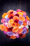 Big round bouquet of colorful roses on a background dark wood. Big round bouquet of colorful roses on a background of dark wood Stock Photos