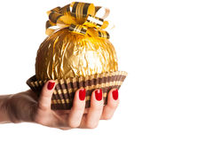 Big round chocolate candy wrapped in golden foil with big bow on Stock Image
