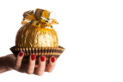 Big round chocolate candy wrapped in golden foil with big bow on Stock Photography