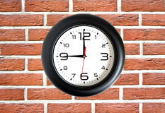Big round clock on red brick wall closeup Royalty Free Stock Photos