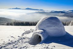 Big round igloo stands on mountains covered with snow attracting the passing by tourist sight. Stock Photo