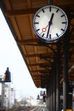 Big round outdoor clock at a railway station. Hanging above Stock Image