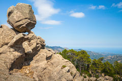 Big round stone lays on top of a coastal rock Royalty Free Stock Photo