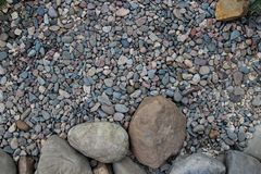 Big round stones and small pebbles of different shape and color. As a background Royalty Free Stock Photos