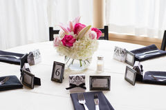 Big round table decorated for wedding celebration. White table cloth on the table with decor for wedding. around the table are black napkins, silver fork and Royalty Free Stock Photography
