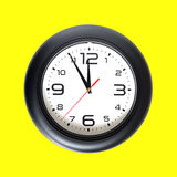 Big round wall clock isolated on yellow close-up Royalty Free Stock Image