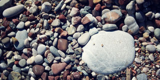 Big round white stone amongst grey and brown pebbles on the beach. Stock Image