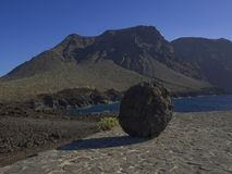 Big rounded lava rock on paved path with view on hight lava clif. Fs los gigantes on Punta de Teno cape on west Tenerife canary island with blue sea and clear Stock Photo