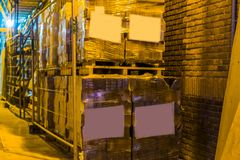 Big row of stacked pallets full of stone tiling, pallets with blank labels, logistics and construction industry background. A big row of stacked pallets full of stock photo