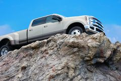 Big rugged pickup truck driving on a rocky cliff ledge Stock Photography