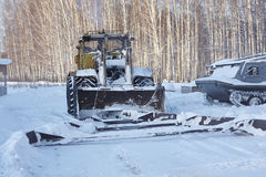 Big russian wheeled tractor with wedge. Forest, snow, sunny day, Russia Stock Image
