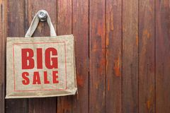 Big sale logo on jute shopping bag hanging over old wooden door background. Business object royalty free stock image