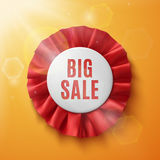 Big sale, realistic red fabric award ribbon. On orange background with sun and sun flares. Badge Royalty Free Stock Photography