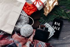 Big sale. special christmas offer discount text on mobile phone. Screen message on seasonal rustic background with cash wallet and bag with stuff. black friday Stock Image