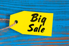 Big Sale tag on blue wooden background. Sales, discount, advertising, marketing price tags for clothes, furnishings Stock Images