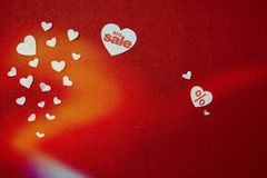 Big sale written on one of the white hearts on a red background near other smaller hearts. Valentines day. Big sale written on one of white hearts on a red royalty free stock photo