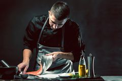 The big salmon is in the hands of the chef cook. He is using a knife to slice salmon fillet stock image