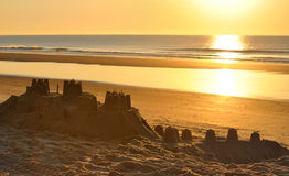Big sand castle on the beach at evening. Sunset over a warm beach and sand castle by the sea stock photo