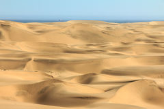 Big sand dunes. Ocean with ships and boat in background. Stock Photos
