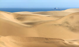 Big sand dunes. Ocean with ships and boat in background. Royalty Free Stock Photos