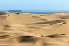 Big sand dunes. Ocean with ships and boat in background. Stock Photography