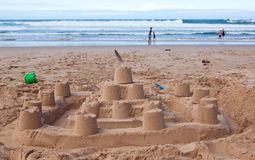 Big sandcastle on the beach with people playing. In the surf Royalty Free Stock Image