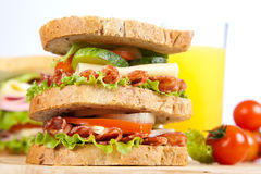 Sandwich. Big sandwich with fresh vegetables on wooden board on white background royalty free stock photography