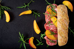 Big sandwich with ham, salami, nectarine and arugula stock photo