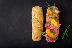 Big sandwich with ham, salami, nectarine and arugula. royalty free stock photography