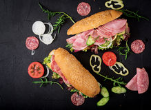 Big sandwich with ham, salami, tomato, cucumber and herbs. Flat lay. Top view royalty free stock images