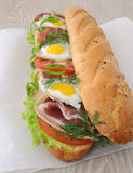 Big sandwich with ham, tomato and quail egg Royalty Free Stock Photos