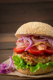 Big sandwich - hamburger with beef, red onion, tomato and fried bacon. Royalty Free Stock Photography