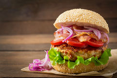 Big sandwich - hamburger with beef, red onion, tomato and fried bacon. Stock Image