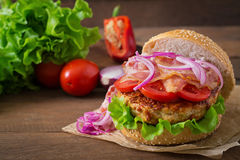 Big sandwich - hamburger with beef, red onion, tomato and fried bacon. Royalty Free Stock Photo