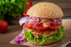 Big sandwich - hamburger with beef, red onion, tomato and fried bacon. Royalty Free Stock Images