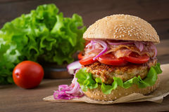 Big sandwich - hamburger with beef, red onion, tomato and fried bacon. Stock Photography