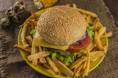 Big sandwich - hamburger burger with beef, cheese, tomato. On a wooden rustic background. Close-up Royalty Free Stock Photo